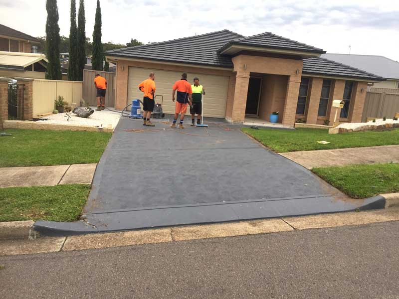 workers standing on new concrete driveway