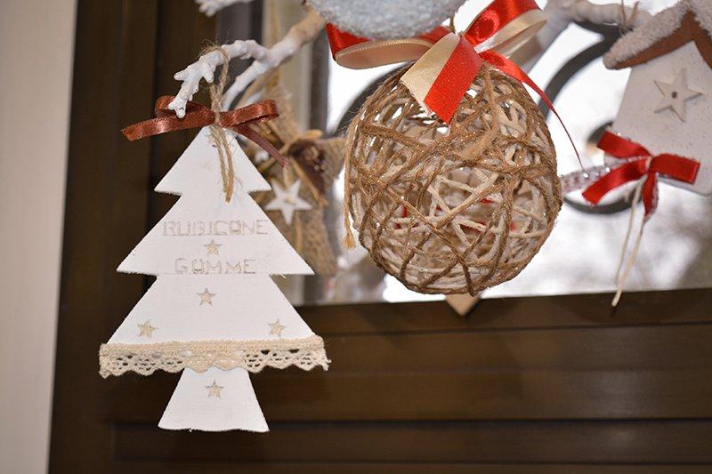 vista ravvicinata di un alberello di Natale in cartone bianco con scritto Rubicone Gomme e accanto altre decorazioni