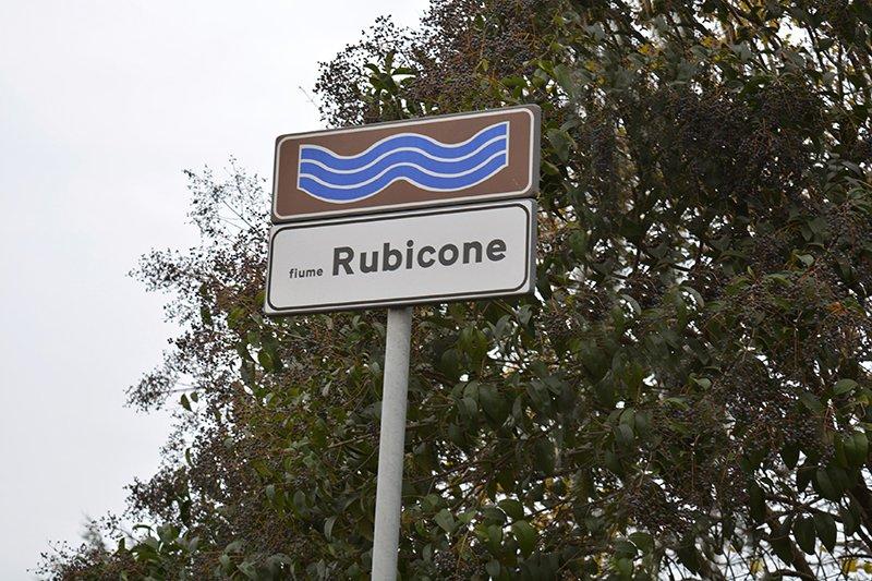 un cartello stradale raffigurante un fiume con scritto Rubicone e dietro un albero