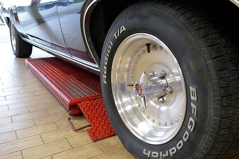 vista laterale di due pneumatici della marca Bf Goodrich di una macchina su un ponte rosso