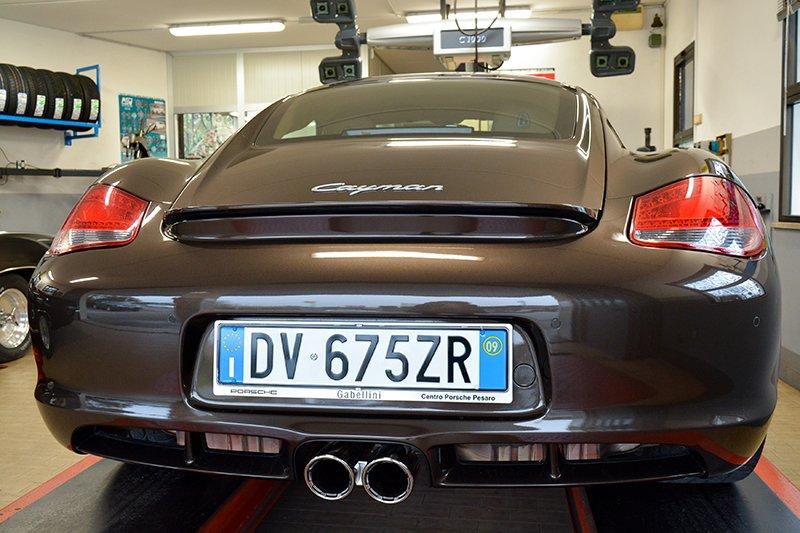vista dal dietro di una Porsche Cayman color nero all'interno dell'officina