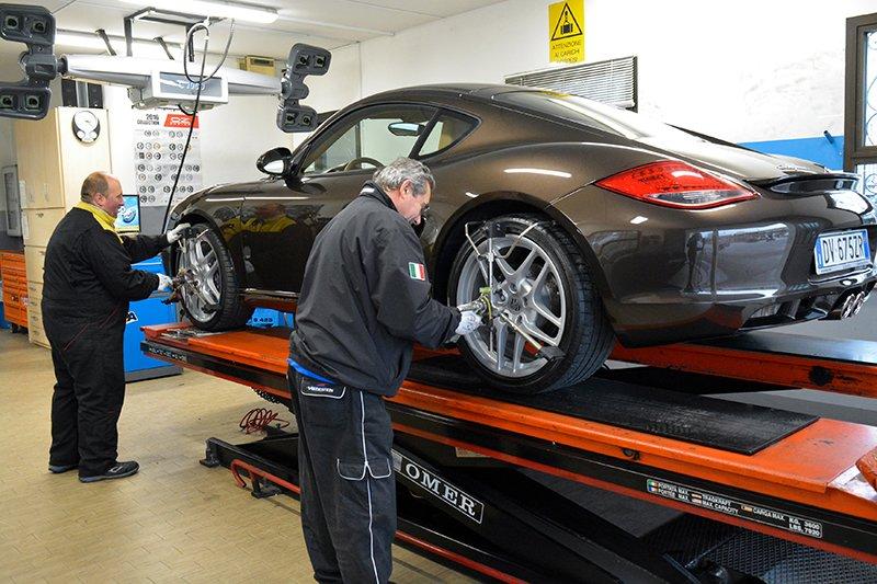due gommisti con delle tute nere al lavoro sui pneumatici di una Porsche Cayman messa sul ponte elevatore