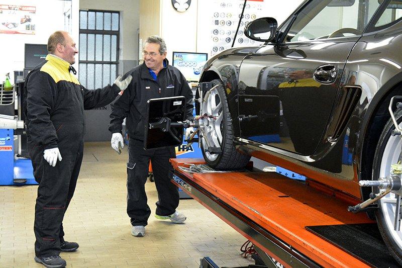 due gommisti che parlano affianco a una Porsche Cayman sul ponte elevatore