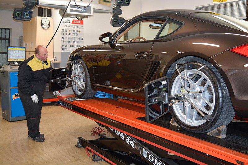 un gommista sta osservando la parte anteriore di una Porsche Cayman sul ponte elevatore