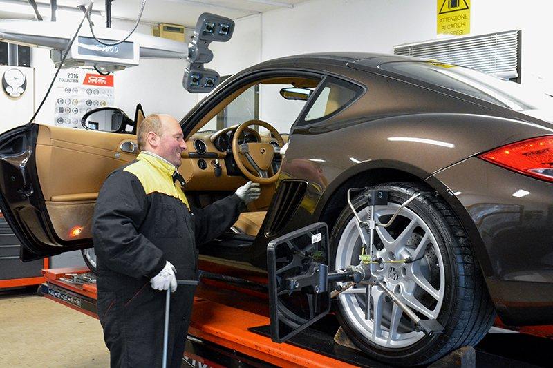 un gommista guarda gli interni con la portiera aperta di una Porsche Cayman sul ponte elevatore