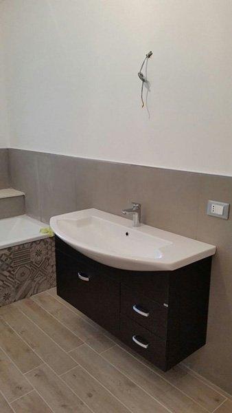 Bagno con pavimento e mobili di legno con le pareti in marrone fino a mezza altezza e piastrelle bruni con disegni differenti