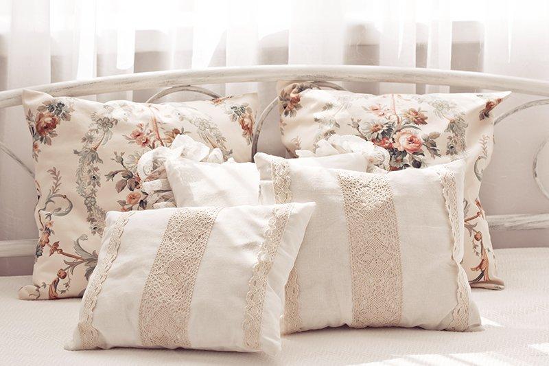 dei cuscini bianchi e alcuni con disegni a fiori
