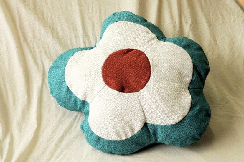 un cuscino a forma di fiore blu,bianco e rosso