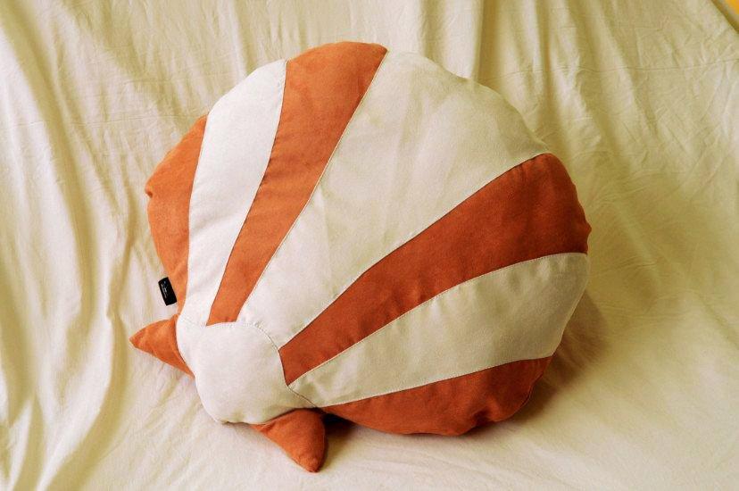 un cuscino a forma di conchiglia bianco e arancione