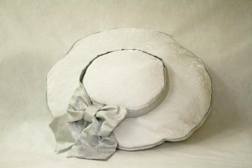 un cuscino bianco rotondo con un fiocco grigio