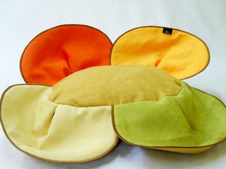 un cuscino a forma di fiore con i petali aperti di color beige,verde,arancione e rosso