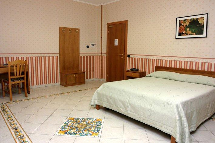 una stanza con un letto matrimoniale e una scrivania
