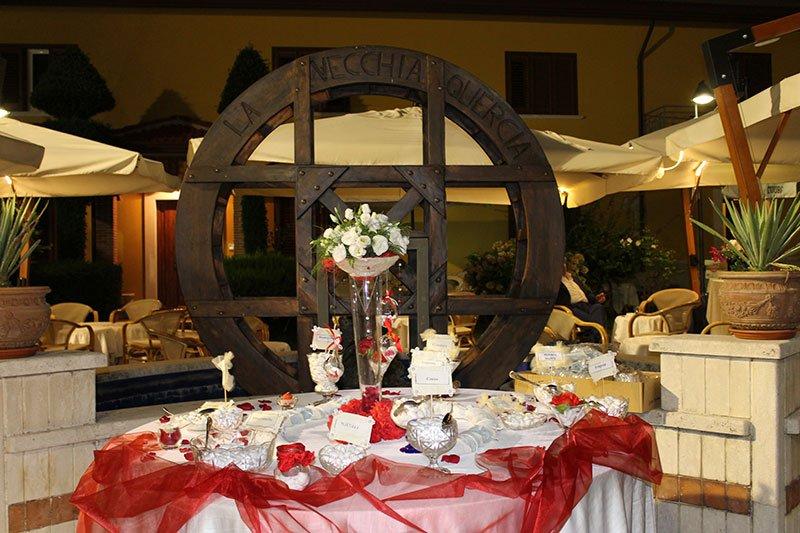 un tavolo decorato con velo rosso e dei vasi con dei confetti