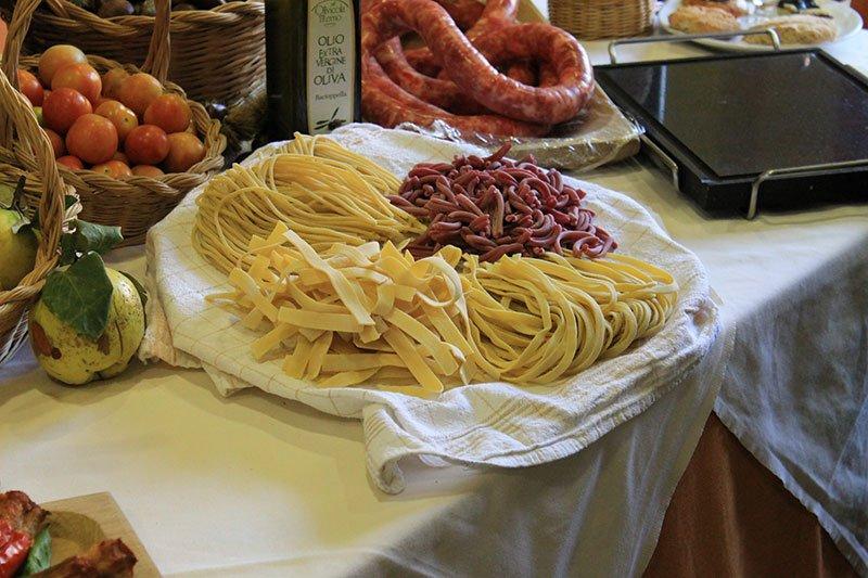un vassoio con la pasta fresca e accanto dei pomodori e delle salsiccie