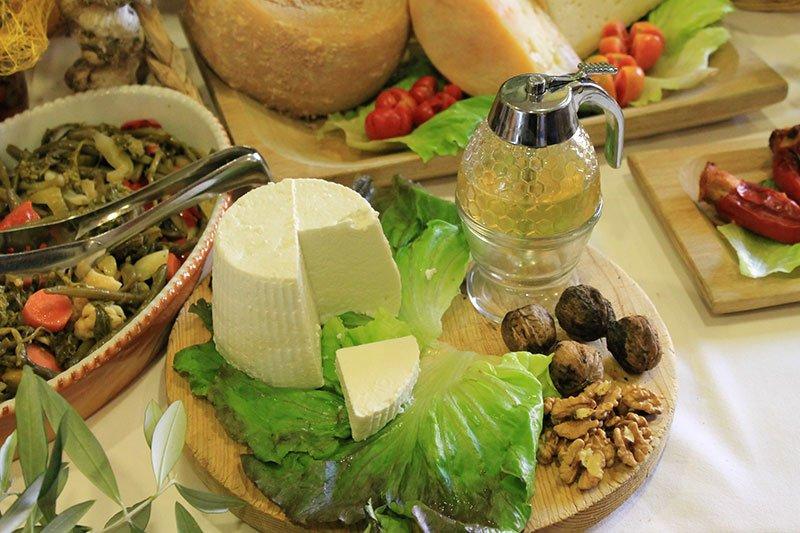 un tagliere con ricotta, noci, insalata e dell'olio di oliva
