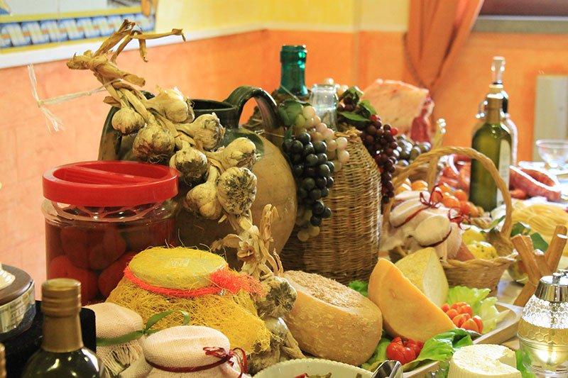 un tavolo con dei formaggi, olio di oliva e altri prodotti