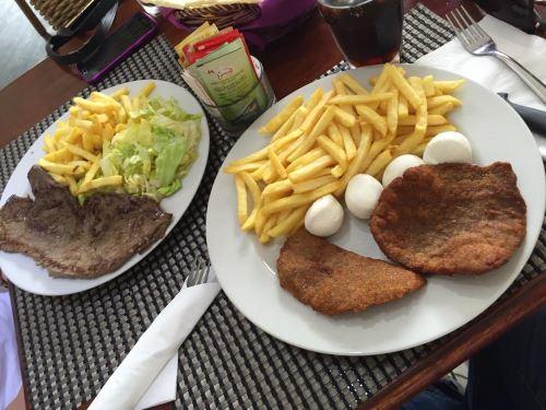due piatti di carne e patatine fritte