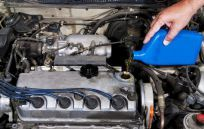 A mechanic adding oil as part of auto maintenance service in Randleman, NC