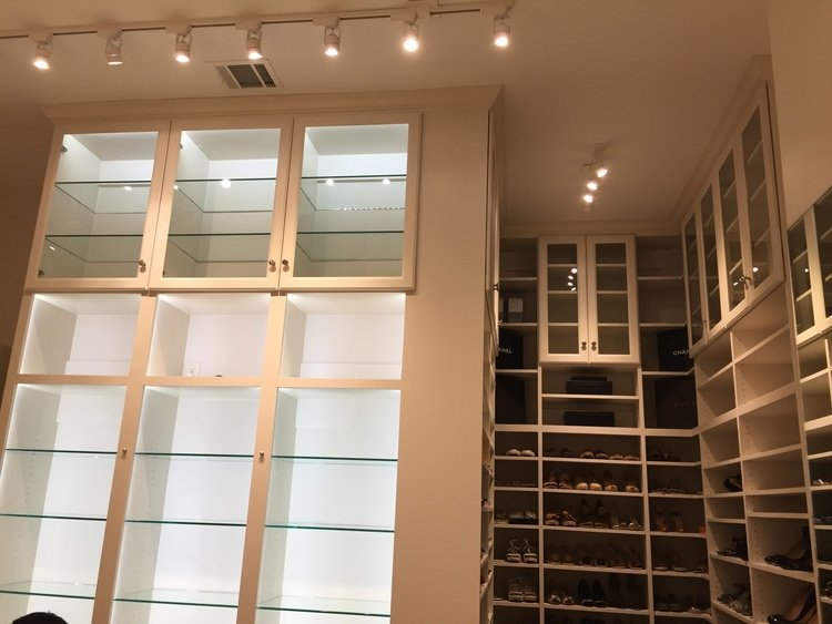 floor to ceiling closet with lighted glass purse shelving