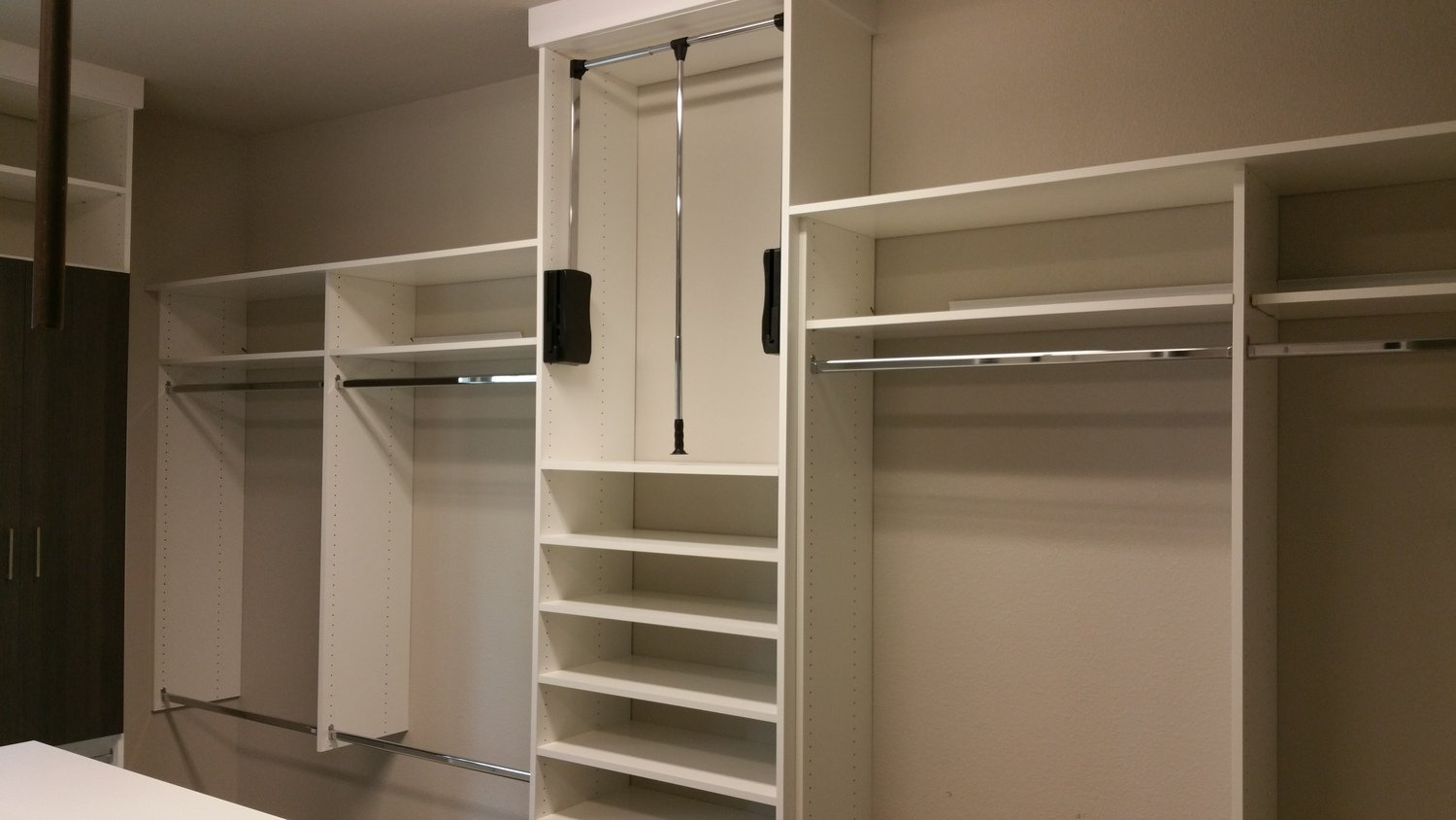 white closet with pull down hanging storage