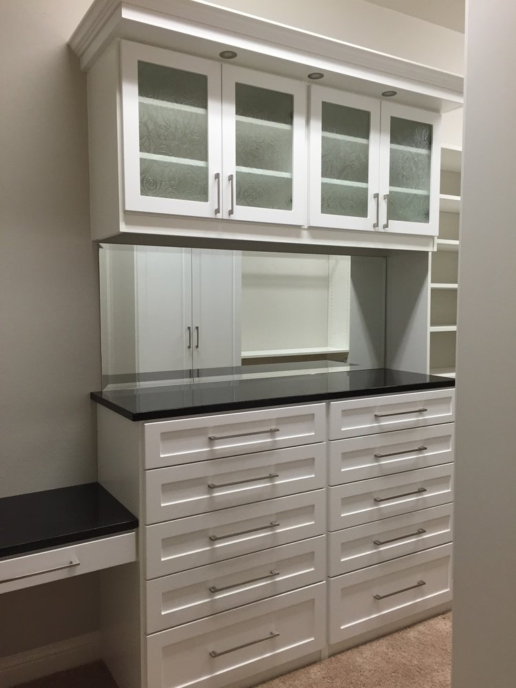 white shaker closet with granite top and LED lighting