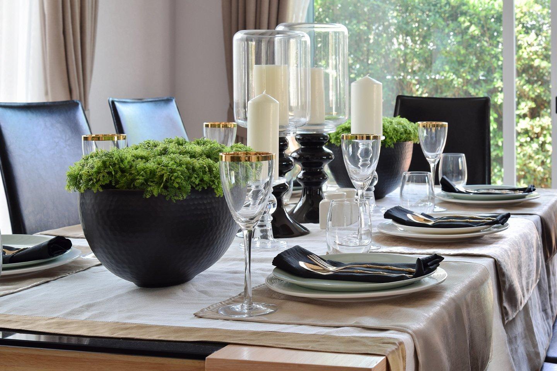 tavolo da pranzo apparecchiato con piatti e bicchieri in vetro