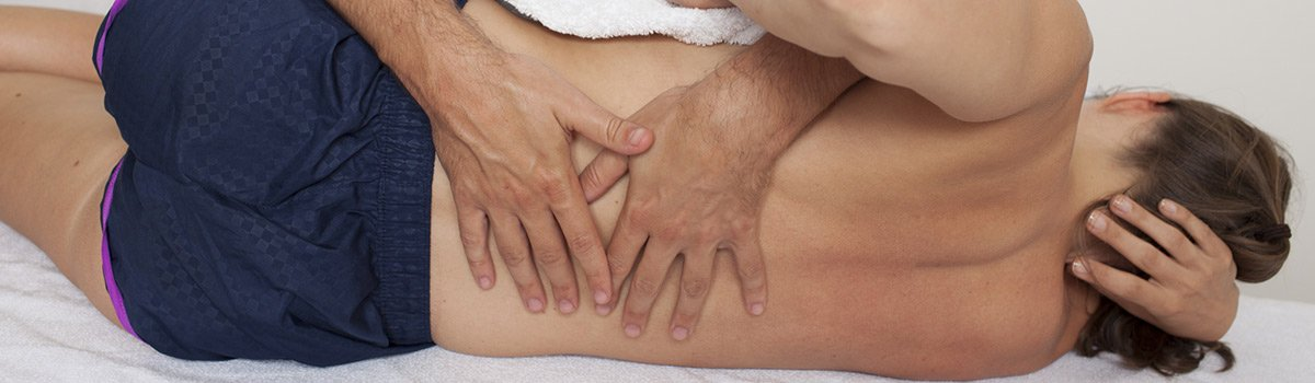 A woman receiving back pain treatment in Bunbury