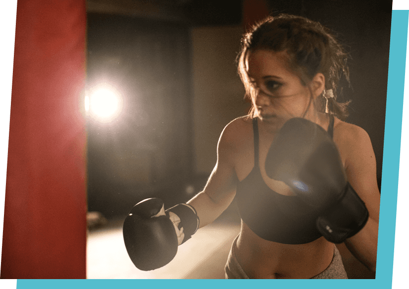 Women boxing on a sand bag