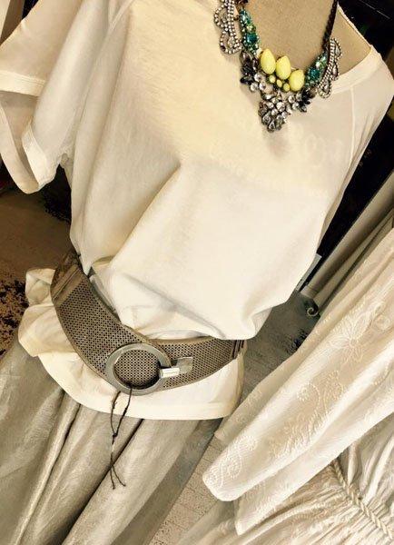 Blouse bianca e gonna grigia con collana vistosa su un manichino