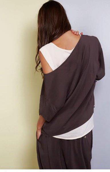 Ragazza di schiena che indossa una maglia larga grigia e una canotta bianca