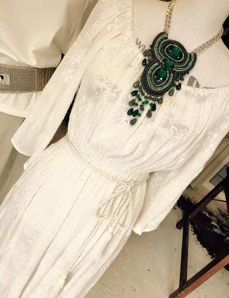 Vestito bianco e collana vistosa verde