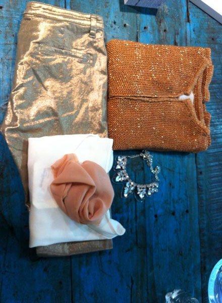 Outfit composto da pantaloni oro, maglioncino arancione, foulard rosa e collana