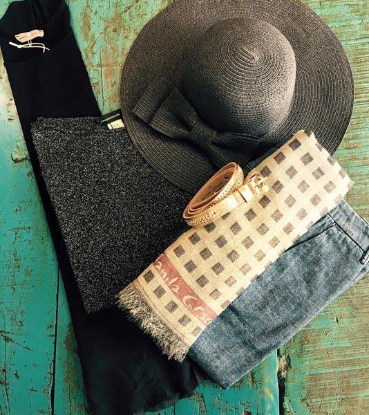 Cappello grigio con fiocco, pantaloni neri, maglioncino grigio, foulard chiaro e cintura marroncino chiaro