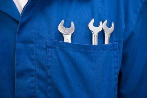 meccanico in tuta blu con chiavi inglesi