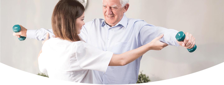 Badante aiuta ad un'anziano a fare gli esercizi fisici a Riccione