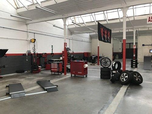 Interno del workshop meccanico con ruote e macchinari