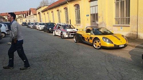 Due auto sportive parcheggiati in strada, uno bianco e un ferrari giallo decappottabile