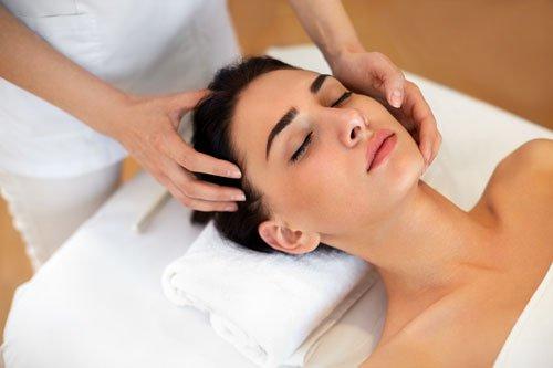 due mani durante un massaggio del viso di una sdraiata su un lettino