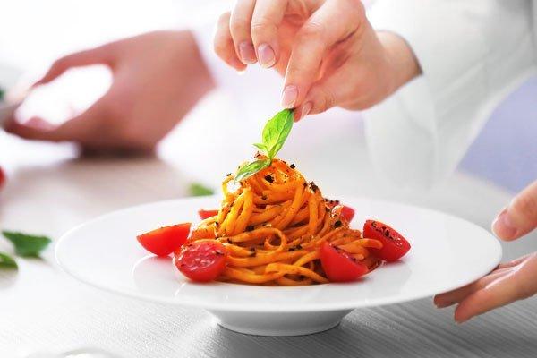 chef che mette una foglia di rosmarino su un piatto di spaghetti al pomodoro