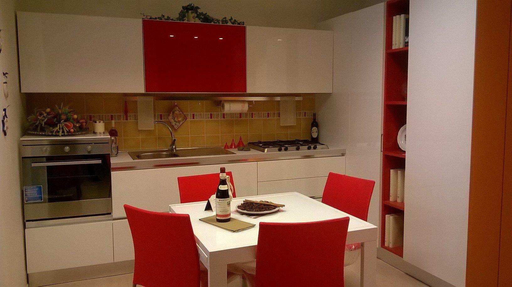 una cucina con mobili bianchi e rossi è un tavolo con le sedie
