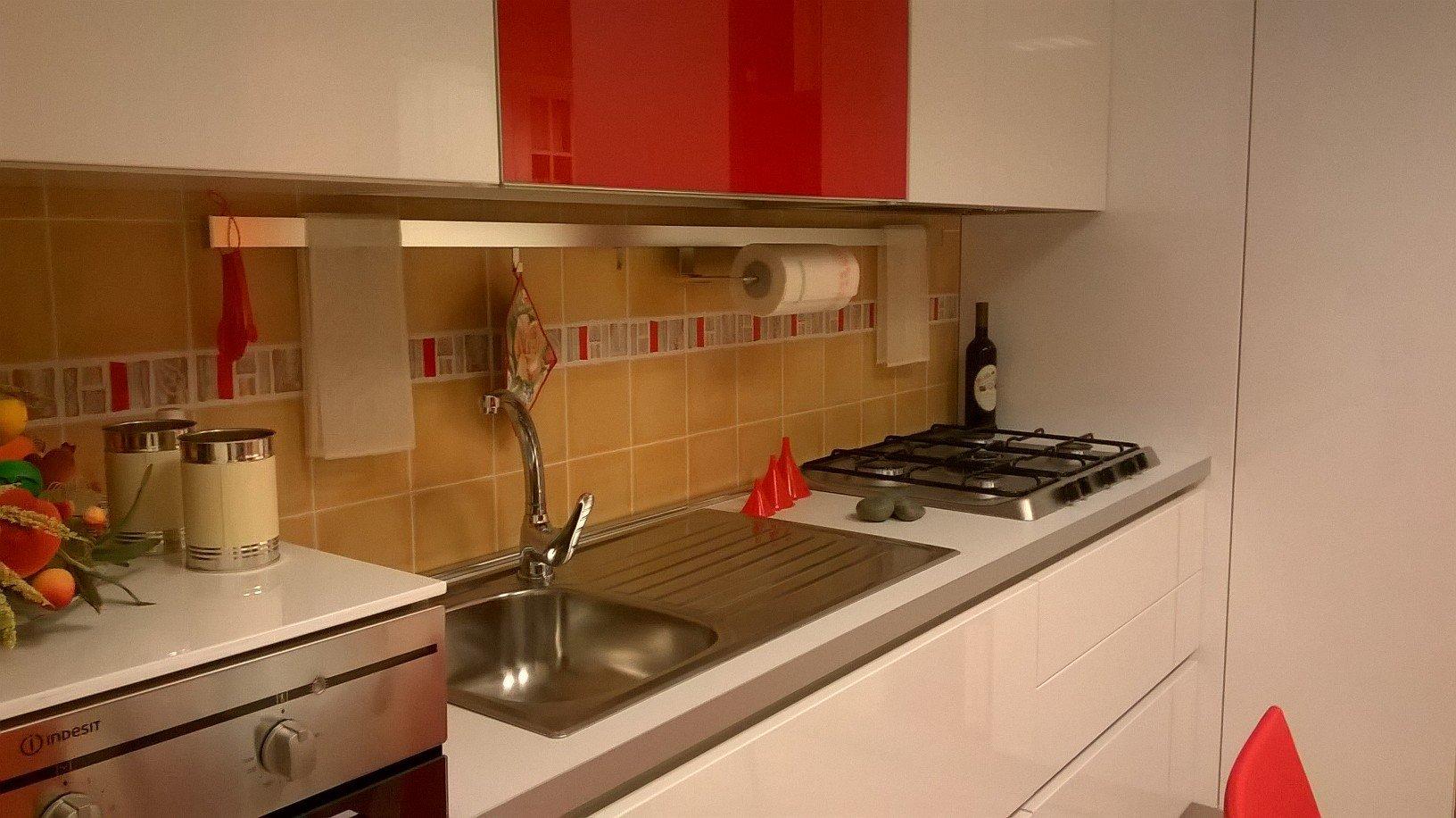 un lavandino e dei fornelli in una cucina con mobili bianchi