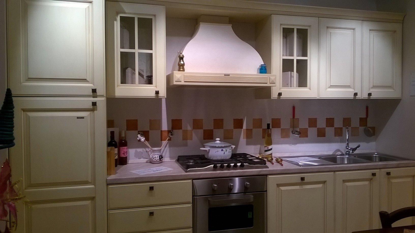 una cucina con mobili in legno color panna