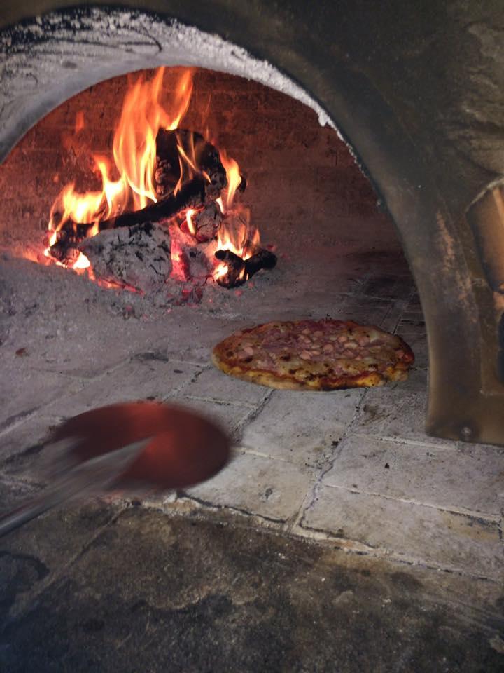 pizza che viene girata nel forno a legna antico