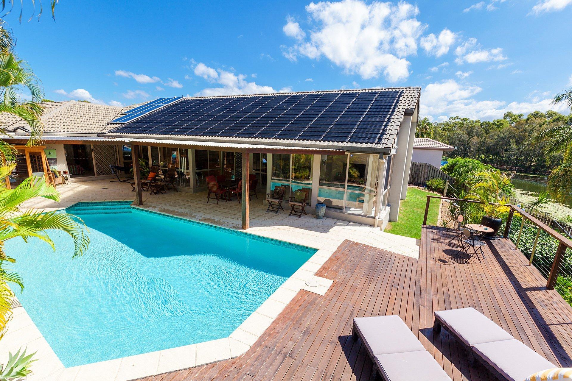 Piscina circondata da piattaforma di legno in una casa il cui tetto è coperto da collettori solari
