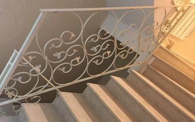 Scale di marmo e ringhiera bianca di ferro battuto