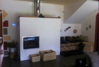 weißer Ofen aus Mauerwerk mit Holzkörben