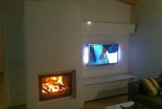 Kamin mit entzündetem Feuer und Fernseher
