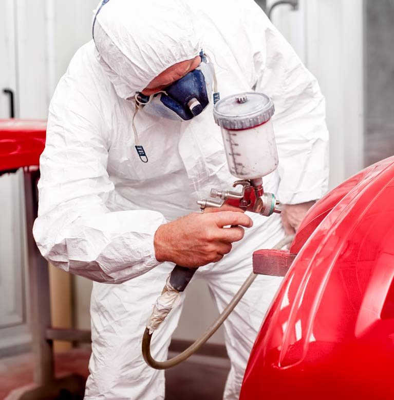man painting car in red