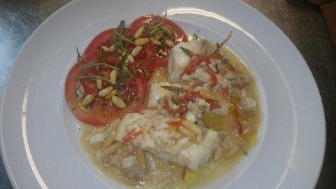pesce con pomodori freschi e pinoli