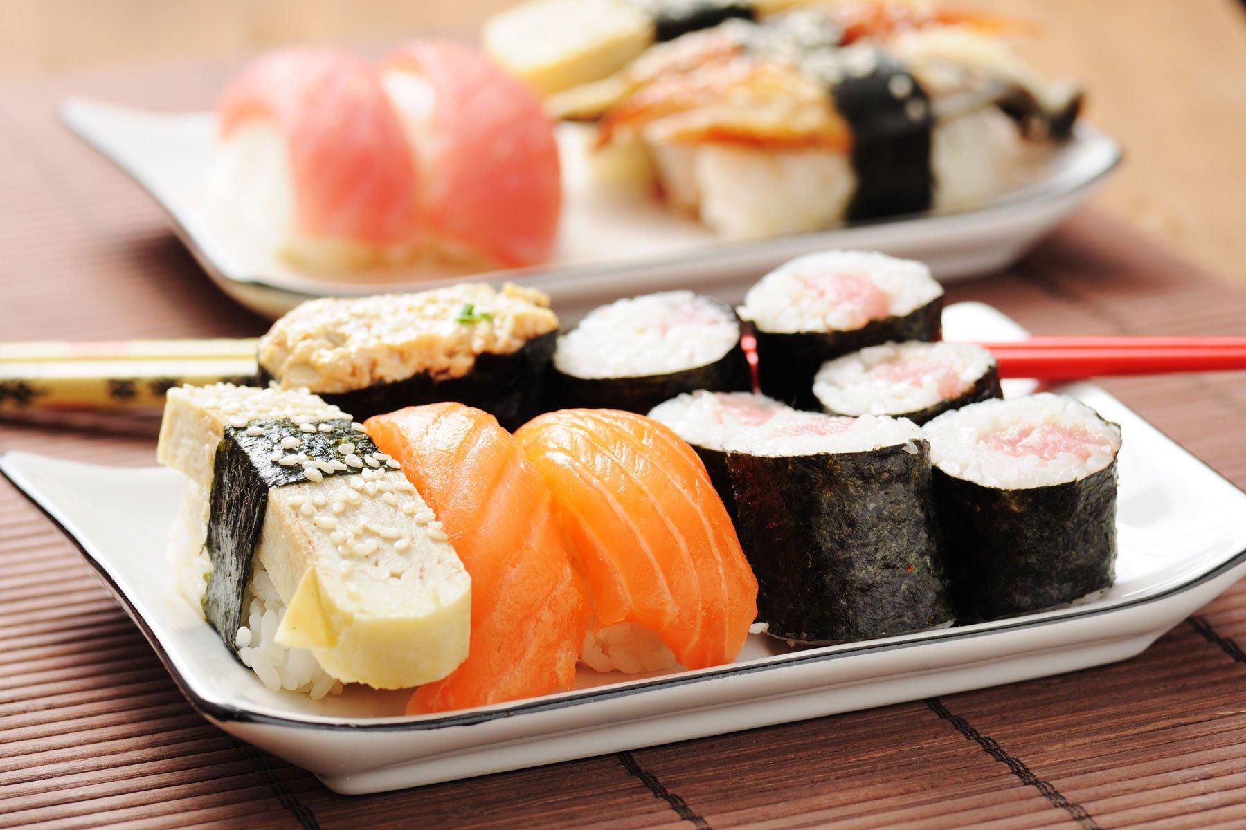 un piatto di sushi con salmone e altre specialità in un piatto bianco su una tovaglietta di bambù